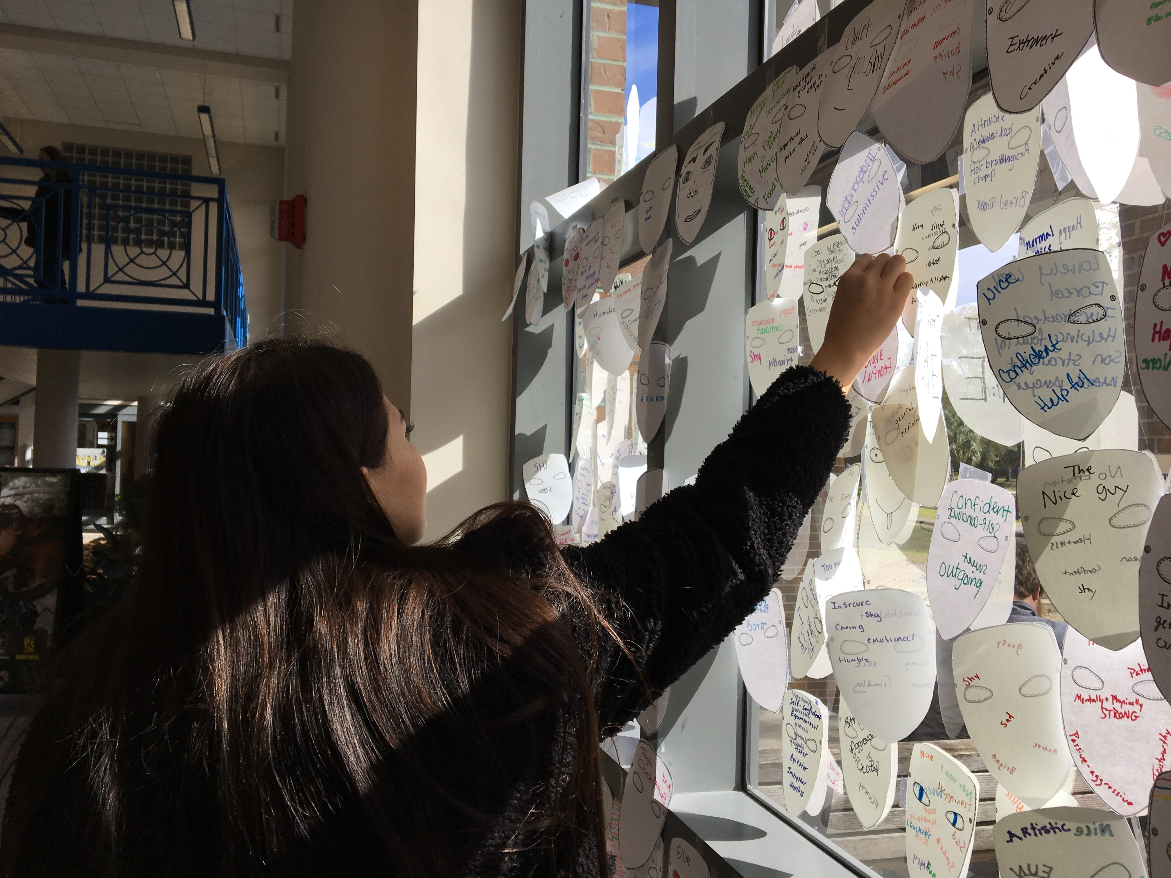"Chloe Stunda, 18, tapes a paper mask to a window inside Tallahassee Community College's Student Union.  Students answered the question, ""What do you show and hide from society?"" by writing qualities on the front and back of the paper mask."