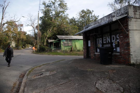 On break from his job in the dining hall at Florida A&M University, Duane Dixie walks past the closed Trends Barbershop and boarded up, abandoned houses to a friend's house on Floral Street in the Bond Neighborhood in Tallahassee Thursday, Nov. 29, 2018.