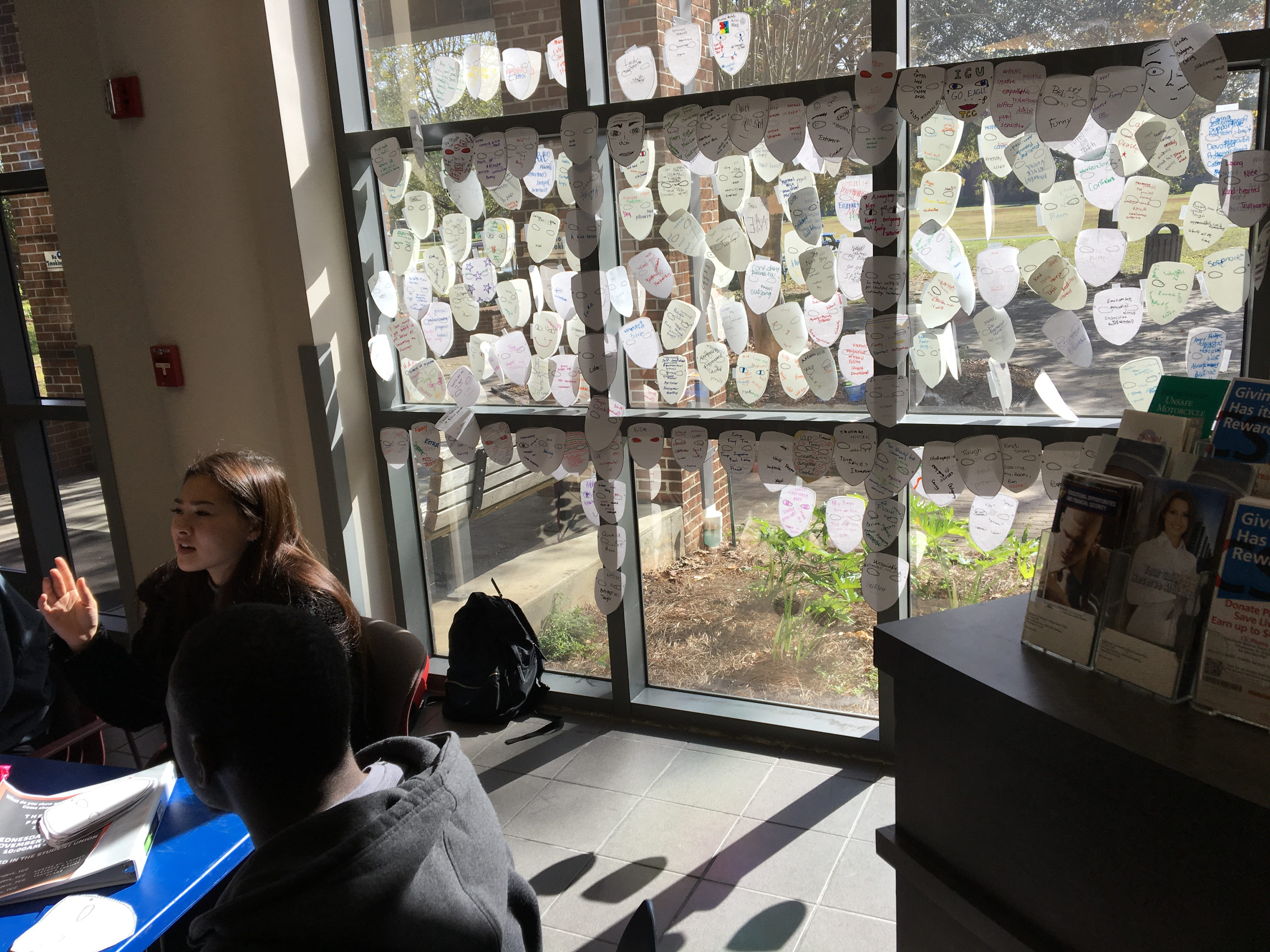 "Paper masks cover the windows for ""Mask Project"" at Tallahassee Community College's Student Union Thursday, Nov. 29, 2018."
