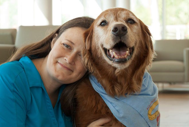 Pet trainer Sheri Anderson and her Golden Retriever, Gabe, the pet therapy dog.
