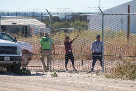 In this Nov. 15, 2018, photo, migrant teens held inside the Tornillo detention camp smile at protesters waving at them outside the fences surrounding the facility. The Trump administration announced in June that it would open the temporary shelter for up to 360 migrant children in this isolated corner of the Texas desert. Less than six months later, the facility has expanded into a detention camp holding thousands of teenagers, and it shows every sign of becoming more permanent.