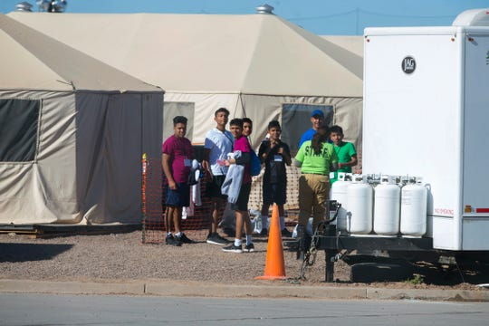 In this Nov. 15, 2018, photo, migrant teens held inside the Tornillo detention camp look at protesters waving at them outside the fences surrounding the facility. The Trump administration announced in June 2018 that it would open the temporary shelter for up to 360 migrant children in this isolated corner of the Texas desert. Less than six months later, the facility had expanded into a detention camp holding thousands of teenagers.