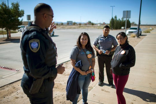 In this Nov. 15, 2018, photo, Dalila Reynoso-Gonzalez, center left, a program director for the Methodist immigration advocacy group Justice for our Neighbors of East Texas, and another protester talk with a Department of Homeland Security official outside the Tornillo detention camp holding more than 2,300 migrant teens. The Trump administration announced in June that it would open the temporary shelter for up to 360 migrant children in this isolated corner of the Texas desert. Less than six months later, the facility has expanded into a detention camp holding thousands of teenagers, and it shows every sign of becoming more permanent.
