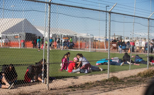 In this Nov. 25, 2018, photo, migrant teens held inside the Tornillo detention camp sit inside the facility.