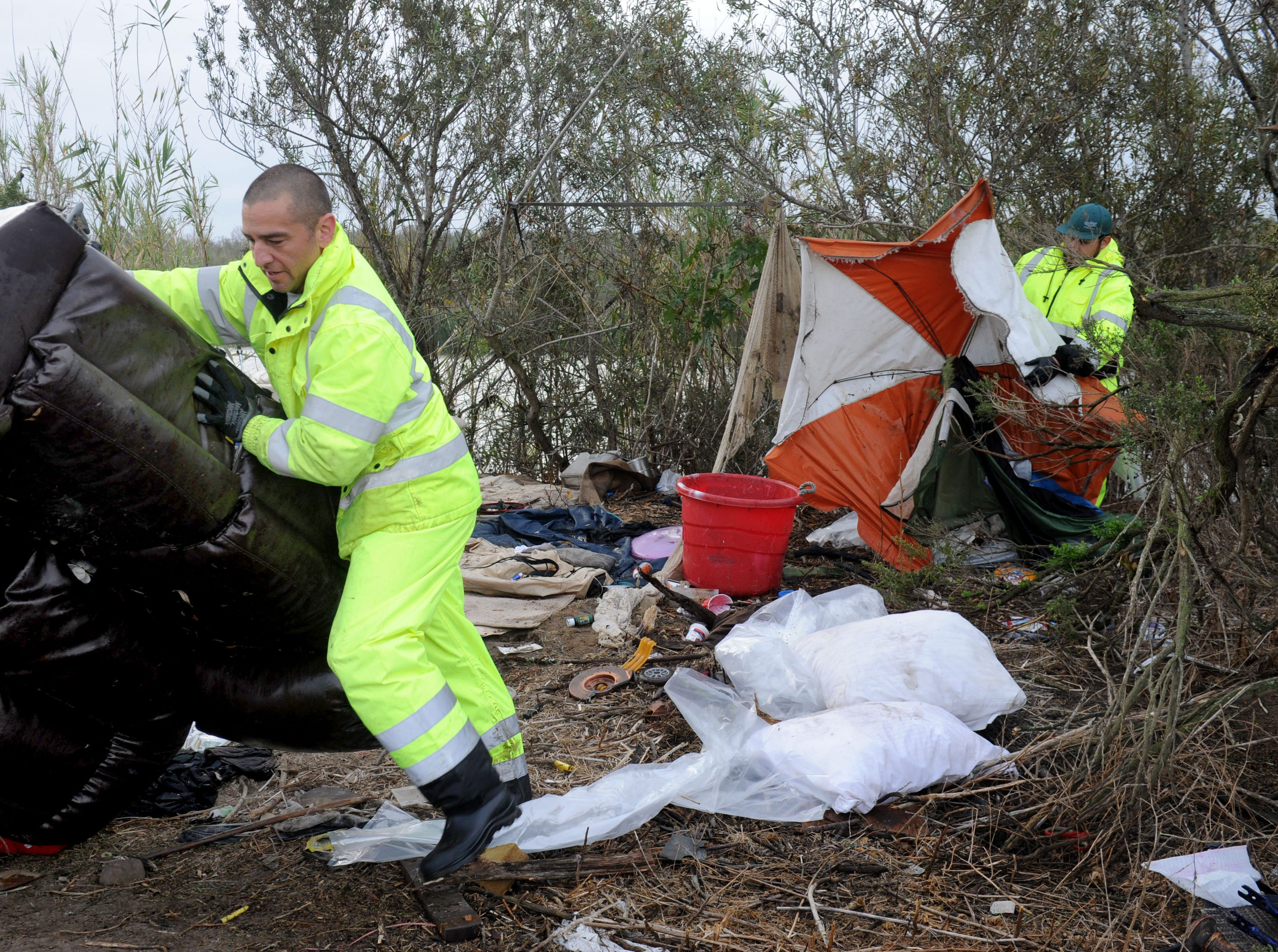 Ventura City employees Ryan Scholle and Sam Ruiz clean up homeless trash Thursday along the Santa Clara River bottom. The city of Ventura organized the effort along the embankment where homeless people live.