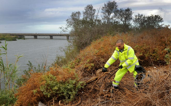 During last week's storm, a Ventura City employee on Thursday worked cleaning up trash along the Santa Clara River bottom where homeless people live.