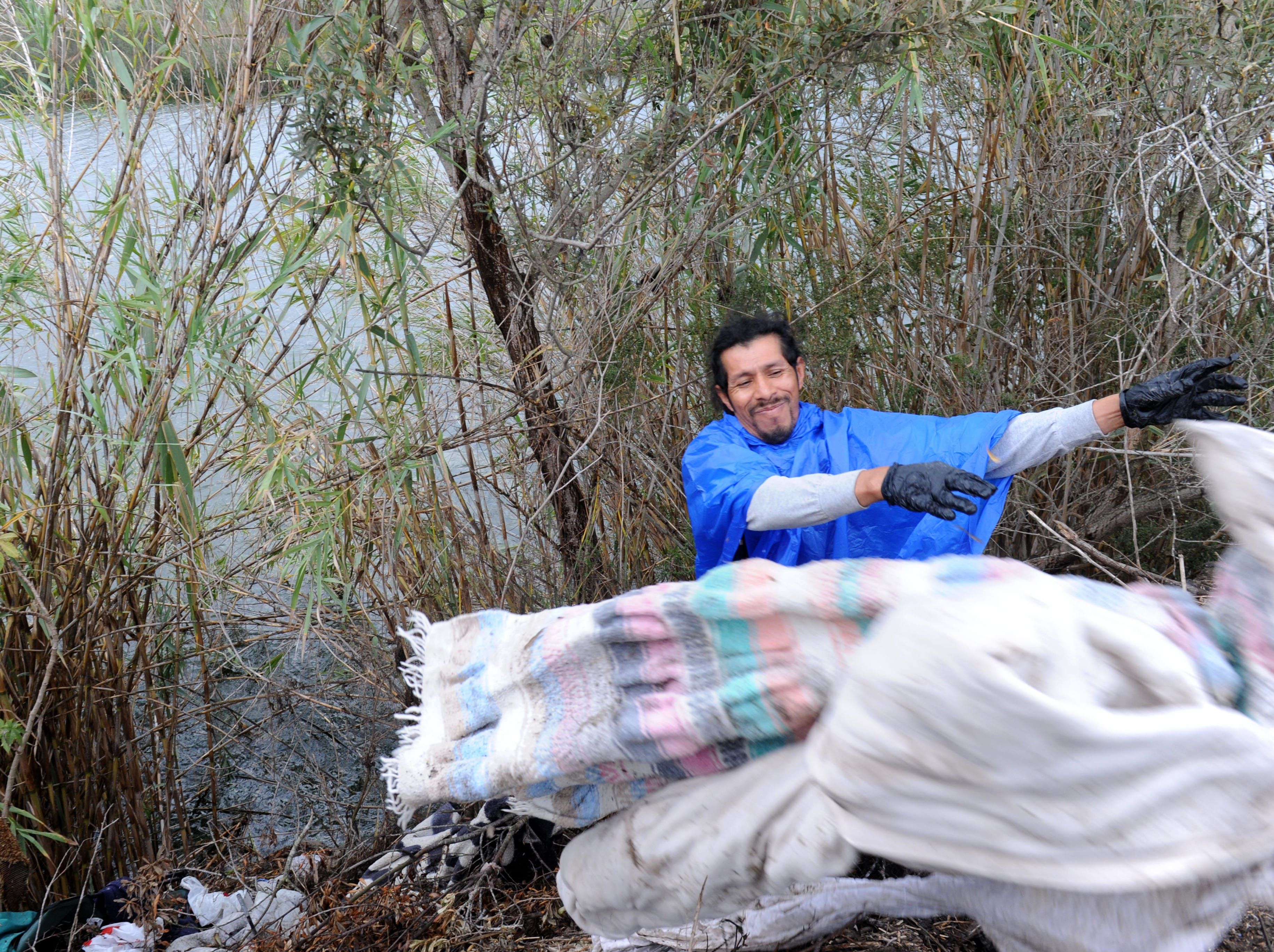 Javier Flores works in the rain Thursday to clear out the Santa Clara River bottom to minimize trash flow to the ocean. The city of Ventura organized the effort along the embankment where homeless people live.