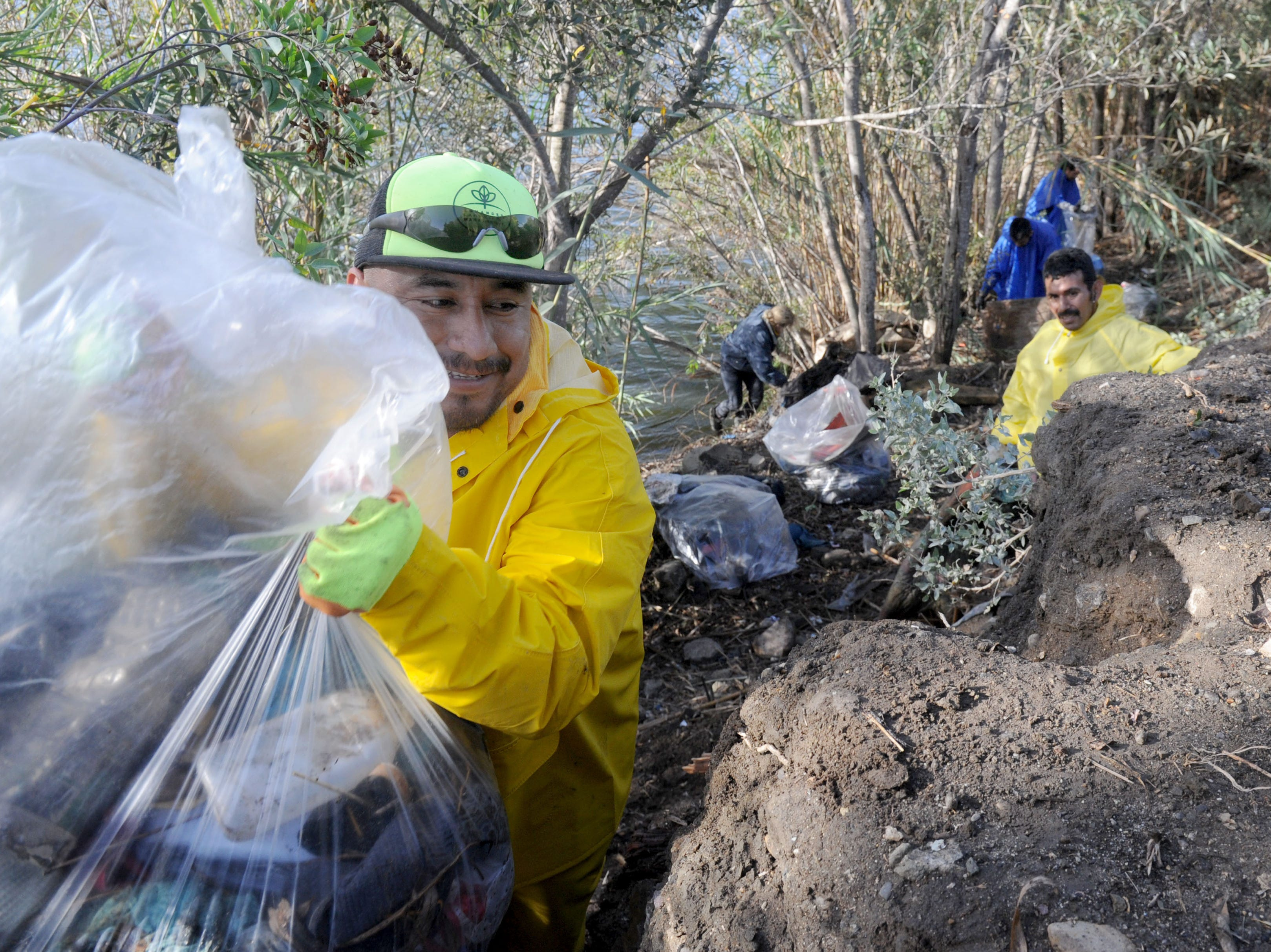Gilberto Santos brings up a trash bag out  of the Santa Clara River bottom. The City of Ventura was the organizer to clean as much trash along the embankment to minimize trash flow to the ocean.