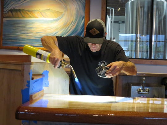 Rincon Brewery co-owner Kevin Clark uses a flashlight and a blow torch to find, and destroy, any errant air bubbles in a newly applied coat of epoxy on the bar at the brewery's Ventura location. It is slated to open by mid-December.