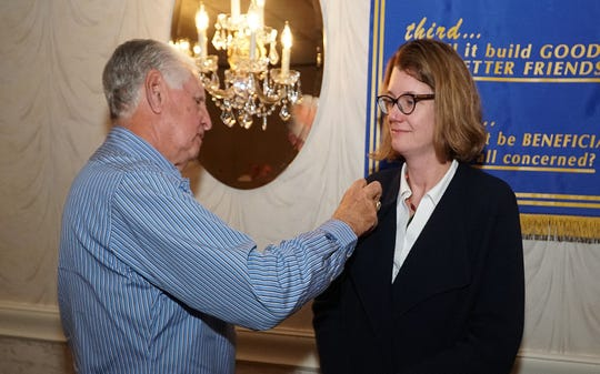 Rev. Heather Sugden, a new member of the Rotary Club of Vineland, receives her Rotary pin from her sponsor, Rotarian Ed Morvay, during a recent club meeting.