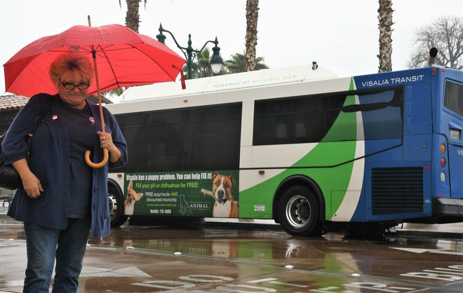 Linda Smith braves the rain in downtown Visalia on November 28, 2018. She says she loves riding in the city's new clean-energy fleet, even when the weather is less than ideal.