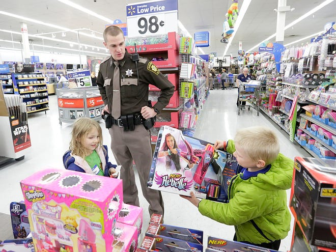 Police officers and children from Fond du Lac participate in a Shop with a Cop event in December 2015.