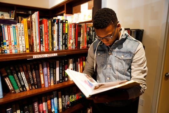 Josephus Gordon, 21, of White Plains, reads a book during his lunch break at  Bronx River Books in Scarsdale on Nov. 29, 2018.
