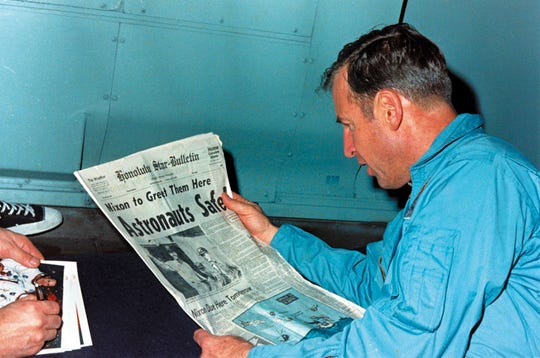 A NASA picture taken on April 17, 1970, shows US Apollo 13 astronaut Jim Lovell aboard USS Iwo Jima reading a newspaper about the crew's successful recovery operations.