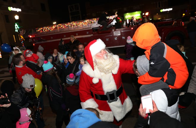 Santa greets a young admirer during Miracle on Main Street in Zanesville Wednesday evening. The parade is just one example of the free or inexpensive holiday actives in the area.