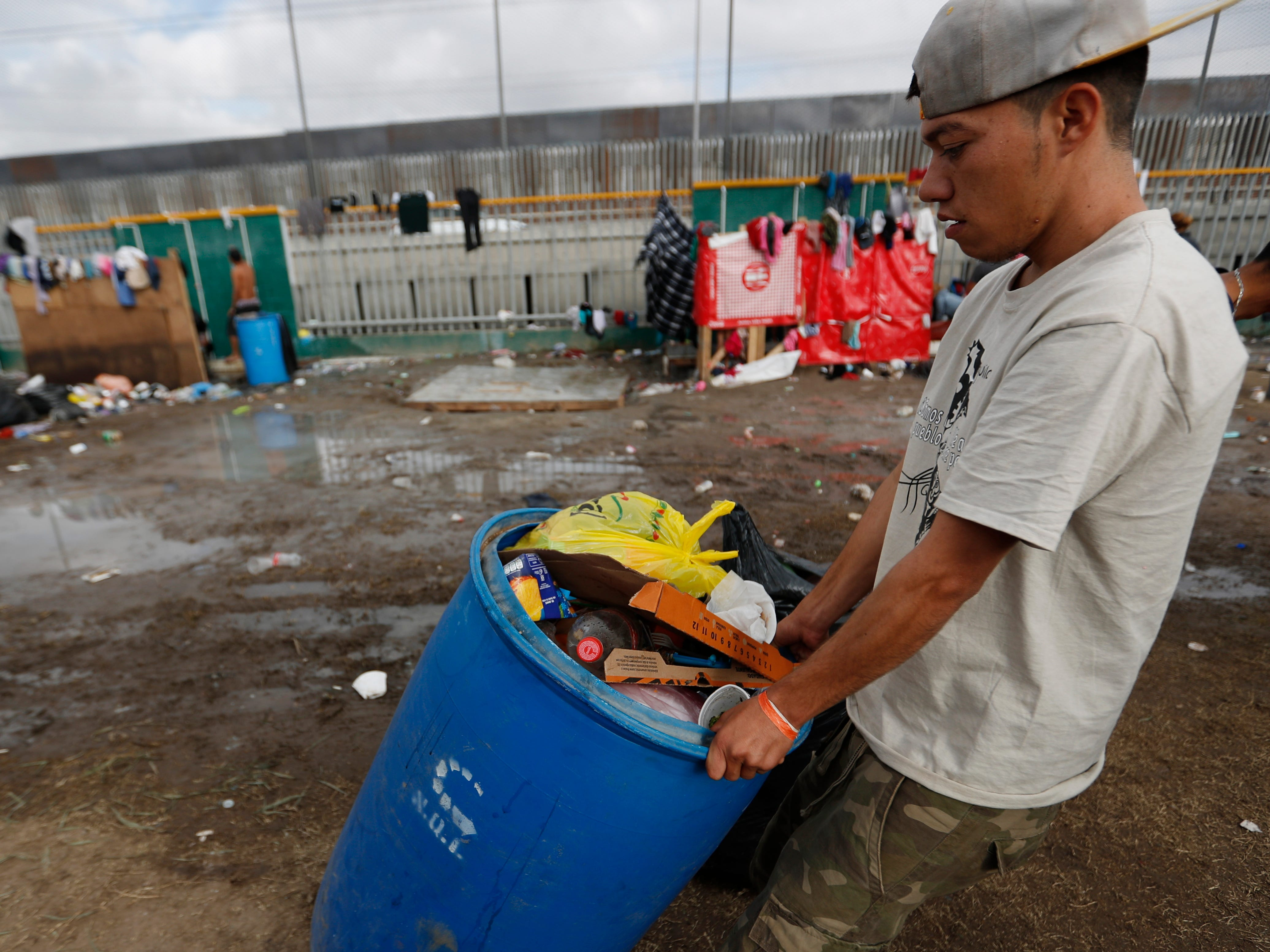 A migrant volunteer hauls trash out past a muddy section inside an overflowing sports complex on Nov. 28, 2018, where more than 5,000 Central American migrants are sheltering, in Tijuana, Mexico.