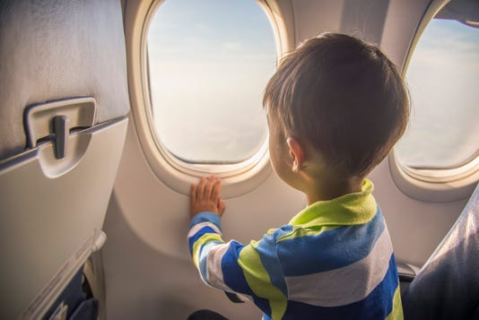 Asian Boy Looking Aerial View Of Sky And Cloud Outside Airplane Window While Sitting On Airplane Seat