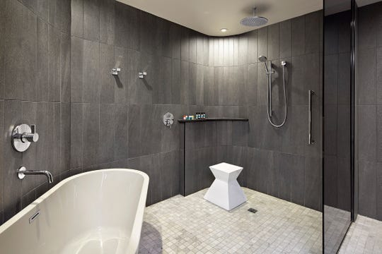 This is a bathtub and a shower at the Statler Dallas, a Curio Collection by Hilton.