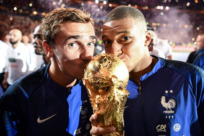 Antoine Griezmann and Kylian Mbappe, right, kiss the World Cup trophy.
