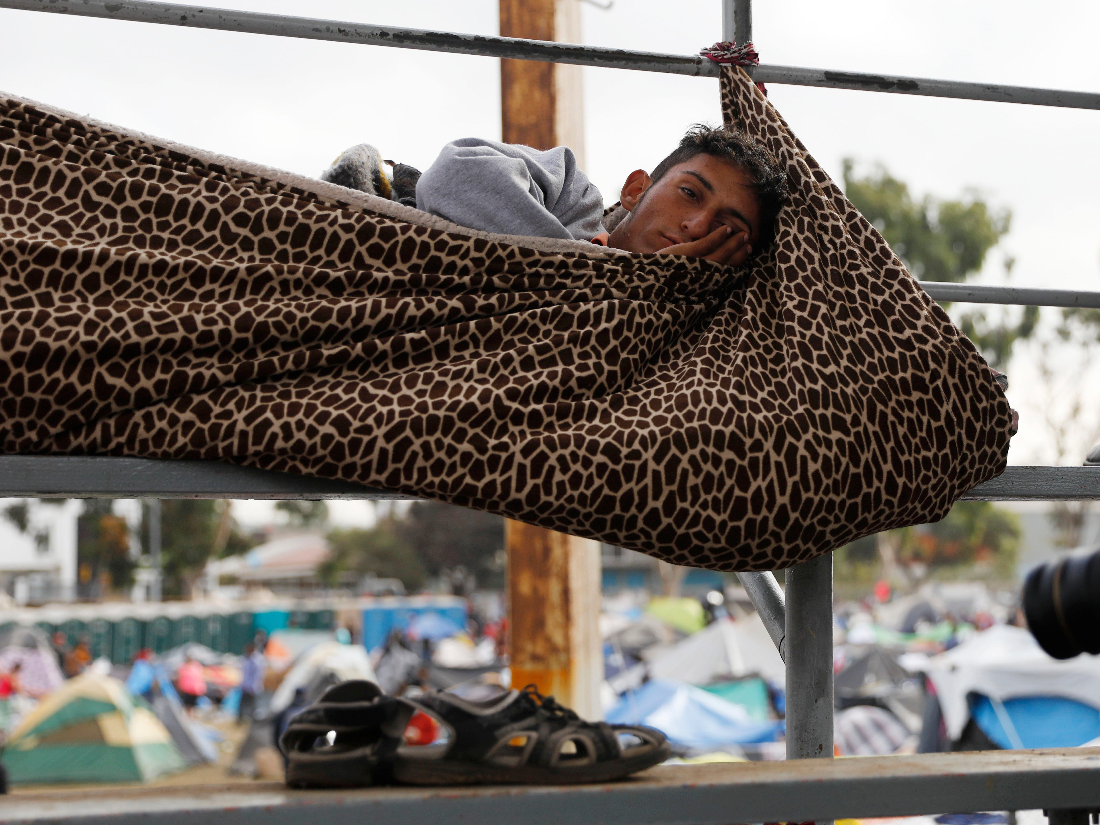 A migrant rests inside a blanket cocoon tied to keep him from rolling off the spectator stands while sleeping, at a sports complex  on Nov. 28, 2018, where more than 5,000 Central American migrants are sheltering, in Tijuana, Mexico.