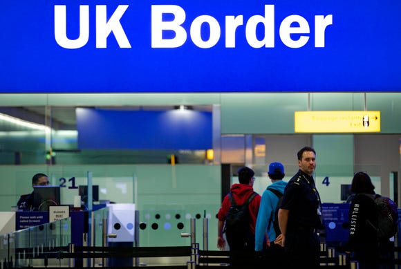 This file photo from March 21, 2017, shows a border patrol officer standing at the British Border crossing in the new Terminal 2 at Heathrow Airport in London.