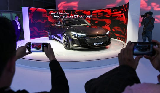 The Audi e-tron GT concept car draws a crowd of people taking snapshots during press preview day at Los Angeles Auto Show.