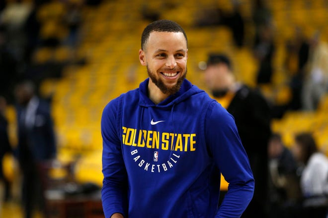 Stephen Curry smiles before the start of a game.