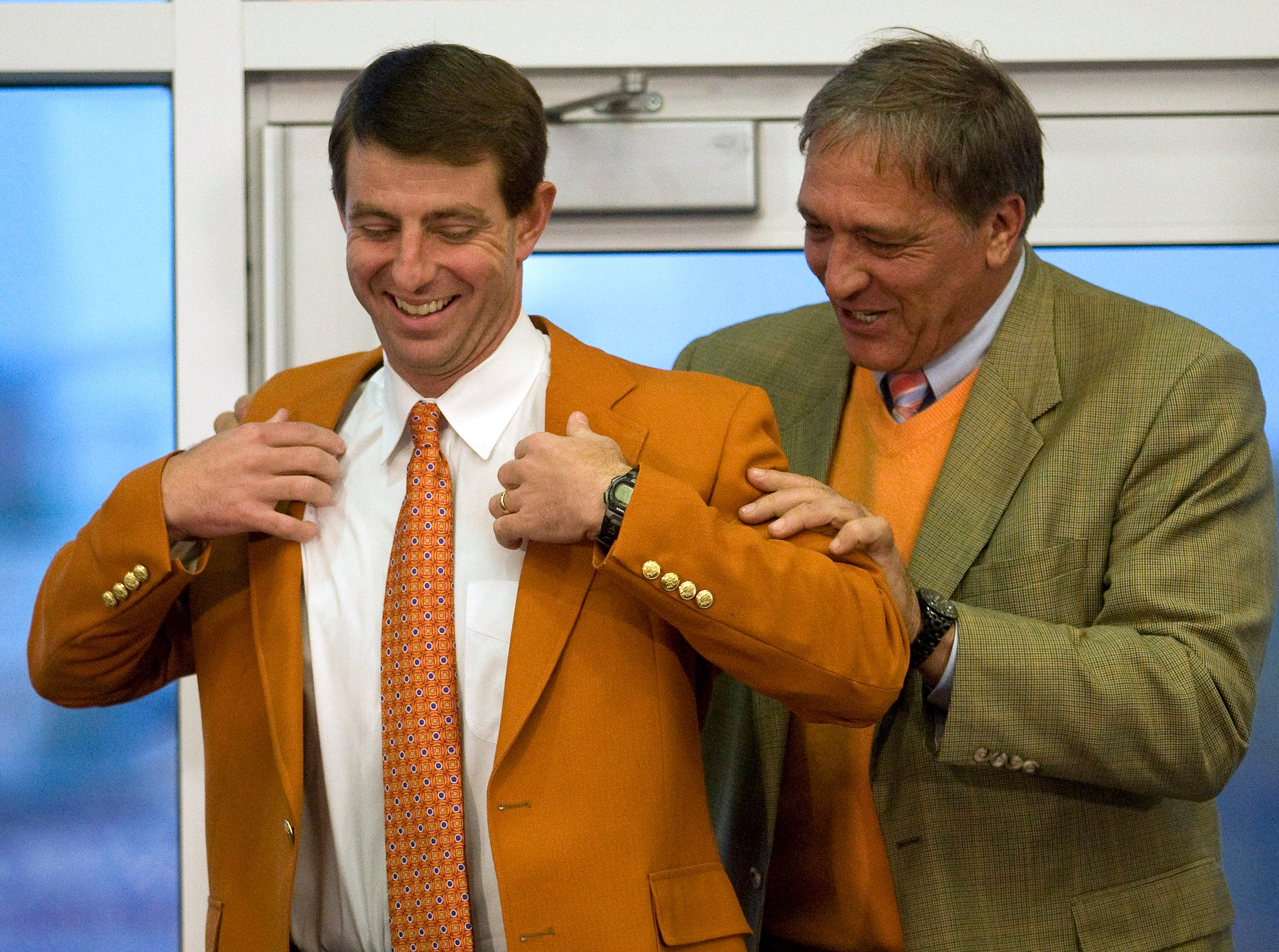 Senior Associate Athletic Director Bill D'Andrea puts an orange blazor on Dabo Swinney during a press conference at Memorial Stadium in Clemson Monday, December 1,  2008 where Swinney was named Clemson's head football coach.