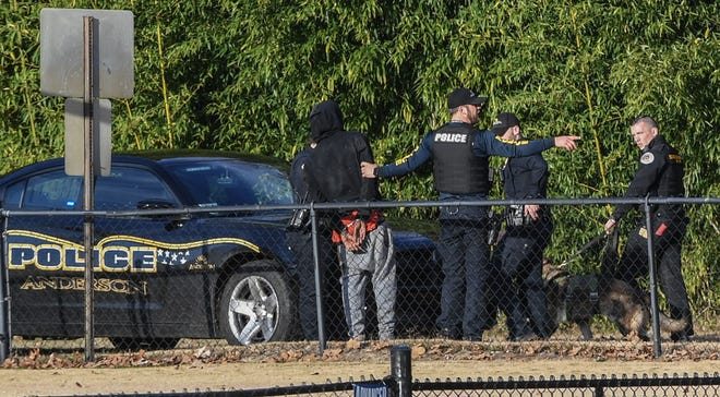 Anderson police hold on to a man in custody while an Anderson County Sheriff's Deputies and K-9 walk by at the former McCants Middle School football field near South Fans Street in Anderson on Friday.