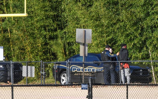 Anderson police escort one of two men in custody at the former McCants Middle School football field to Medshore ambulance workers to get checked on after being chased in Anderson on Friday.