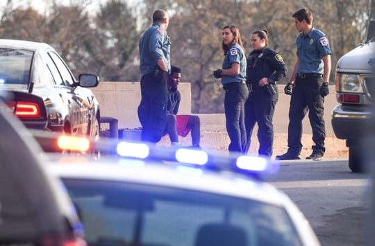 Anderson police stay near one of two men in custody outside a Medshore ambulance at the former McCants Middle School football field parking lot, after being chased in Anderson on Friday.