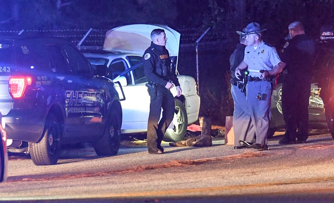 Anderson County Sheriff's Office deputies, investigators and troopers from the State Highway Patrol  work the scene where a  chase ended near T.L. Hanna High School in Anderson on Thursday night.