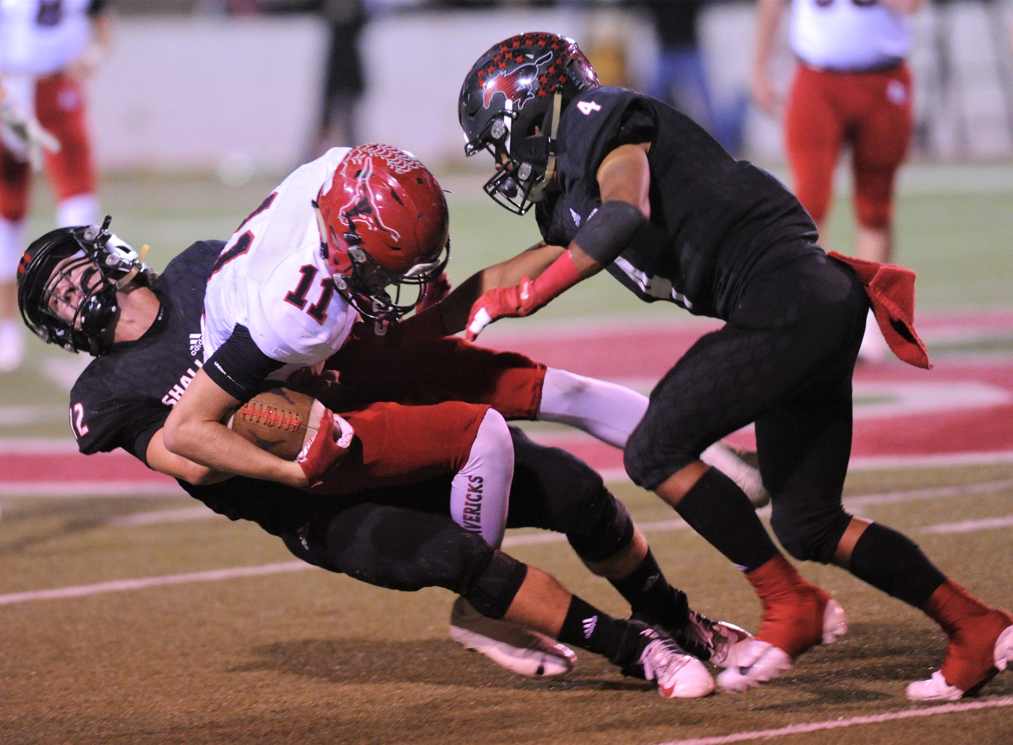 Eastland's Tyler Lucky (11) tackled by a pair of Shallowater players after making a catch. Shallowater beat the Mavericks 56-21 in the Region I-3A Division I semifinal playoff game Thursday, Nov. 29, 2018, at the Mustang Bowl in Sweetwater.