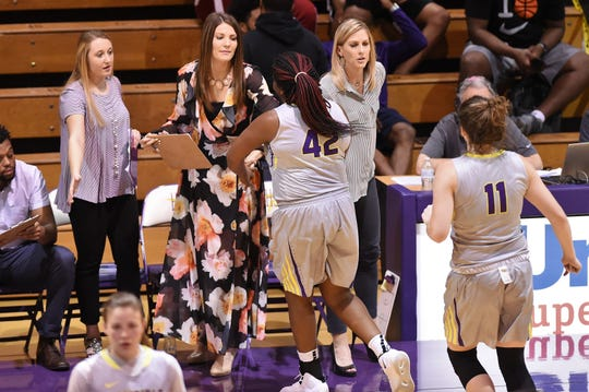 Hardin-Simmons coach Kendra Hassell gives Kiana Reed (42) and Keilee Burke (11) high-fives during a substitution against Louisiana College on Thursday.