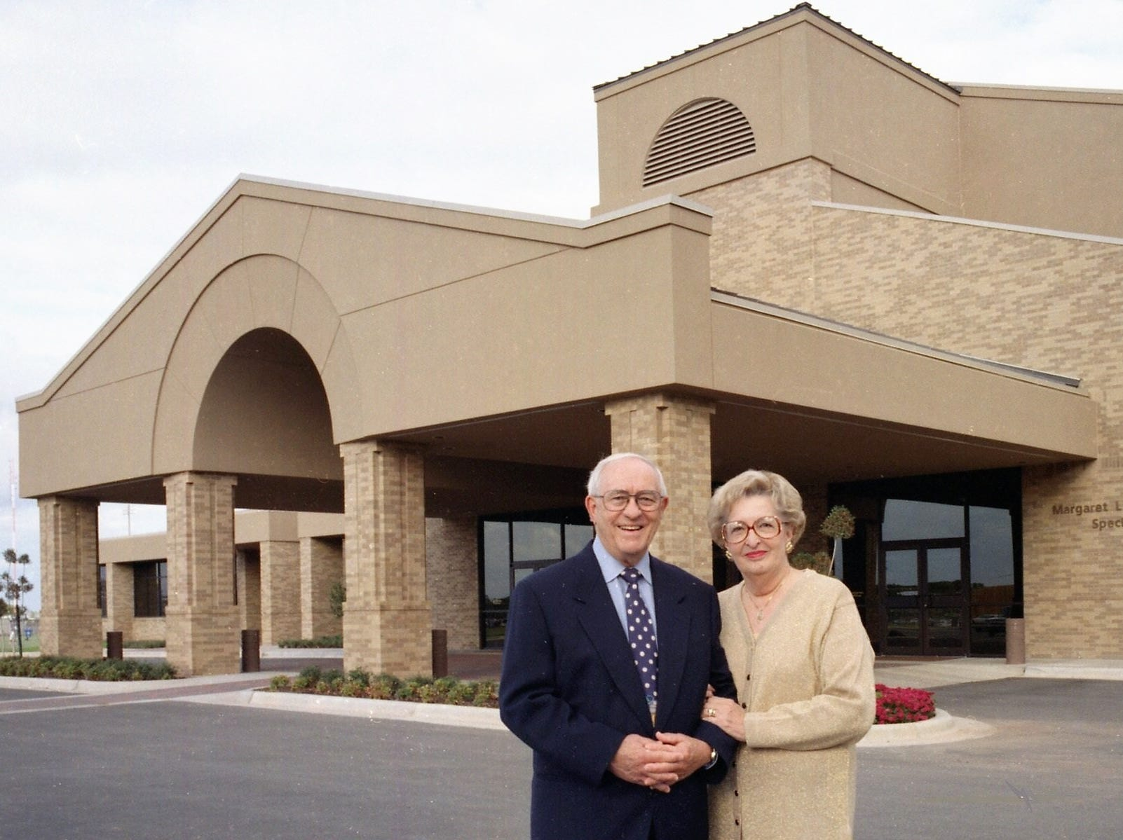 William and Peggy Teague stand in front of the Margaret L. and William J. Teague Special Events Center. It now is the Margaret L. and William J. Teague Center.