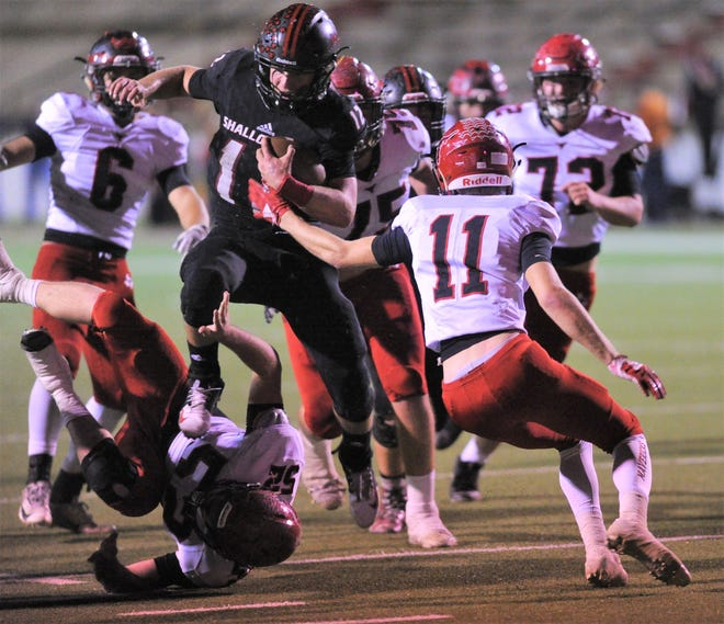 Shallowater quarterback Cutter sparks leaps over Eastland defender Nathaniel Cruz (25) as Tyler Lucky also defends near the end zone. Shallowater beat the Mavericks 56-21 in the Region I-3A Division I semifinal playoff game Thursday, Nov. 29, 2018, at the Mustang Bowl in Sweetwater.