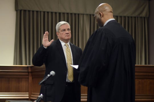 Buncombe County Sheriff Jack Van Duncan listens to Buncombe County Judge Calvin Hill while being sworn in Monday evening Dec. 1, 2014. With Duncan is wife Shana.