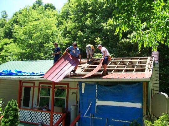 CHC volunteers working to repair a neighbor's roof.