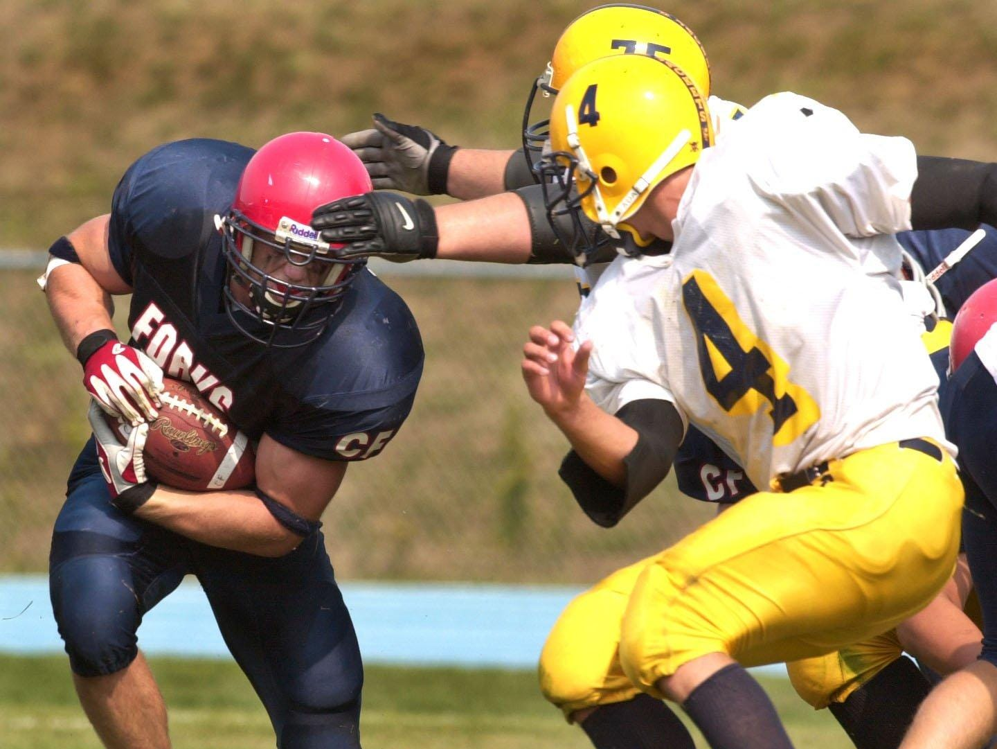 From 2001: Chenango Forks' Kelsey Jenks gets ready to collide with Oneonta's James Hurtubise, 4, and Tony Dilello, 75, (in back) in the second quarter at Chenango Forks.