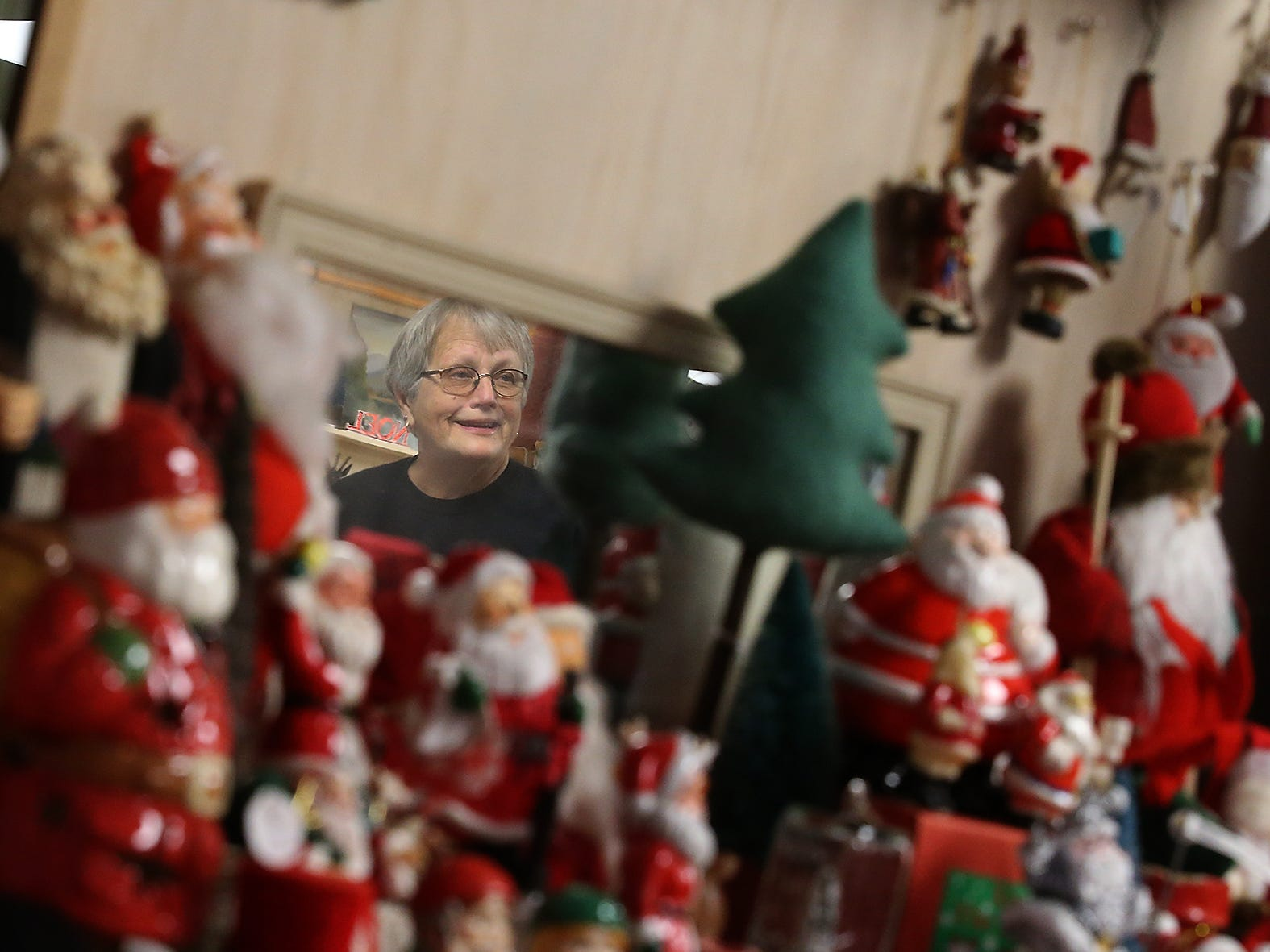 Carolee Pederson is reflected in a mirror surrounded by Santa figurines at The Christmas House/Lemolo Vintage Market in Poulsbo on Wednesday, November 28, 2018.