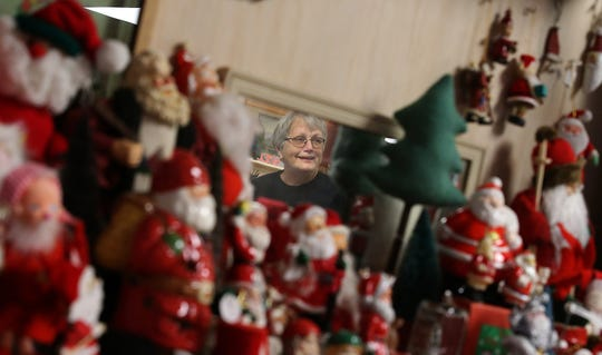 Carolee Pederson is reflected in a mirror surrounded by Santa figurines at Lemolo Vintage Market in North Kitsap.
