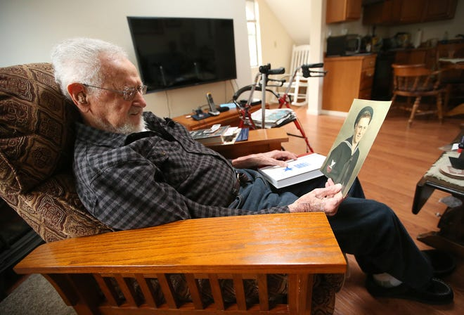 James Villiers, 95, looks at a photograph of himself when he was in the Navy at his home in Suquamish. He was inspired to join after the Japanese attack on Pearl Harbor.