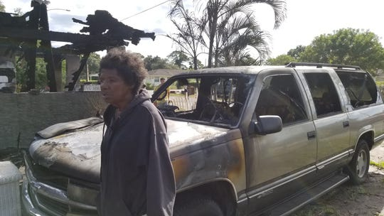 Fort Pierce resident Dianne Hunt stands in front of her ruined SUV. Her home and vehicle were destroyed in a fire early Friday.