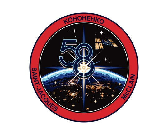 The official insignia for the three-member Expedition 58 crew with Anne McClain of NASA, Oleg Kononenko of Roscosmos and David Saint-Jacques of the Canadian Space Agency.