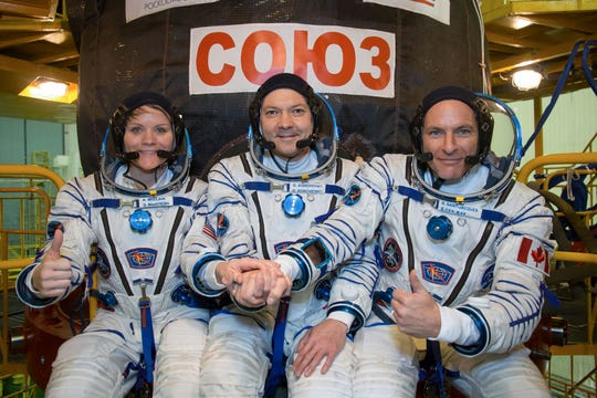 In the Integration Facility at the Baikonur Cosmodrome in Kazakhstan, Expedition 58 crew members Anne McClain of NASA (left), Oleg Kononenko of Roscosmos (center) and David Saint-Jacques of the Canadian Space Agency (right) posed for pictures Nov. 20 in front of their Soyuz MS-11 spacecraft during a vehicle fit check. They will launch Dec. 3 on the Soyuz MS-11 spacecraft from Baikonur for a six-and-a-half month mission on the International Space Station.