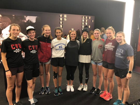 The CVU girls cross-country team poses with professional runners with Shalane Flanagan and Shelby Houlihan in Beaverton, Oregon, on Thursday.
