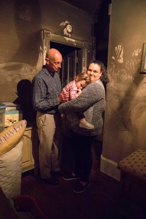 Eva Ray lays on her grandmother Mindy Martin's shoulders as her grandfather Ray Martin comforts her. The family is standing in the once light blue hallway outside the bedroom where a fire was caused by a humidifier.