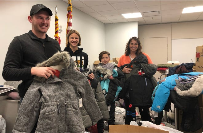 Justin Draise, Isaac Crawford, Deacon Crawford and Stephanie Draise sort through and prepare to deliver more than 1,000 new coats purchased by Adena caregivers for area school children.