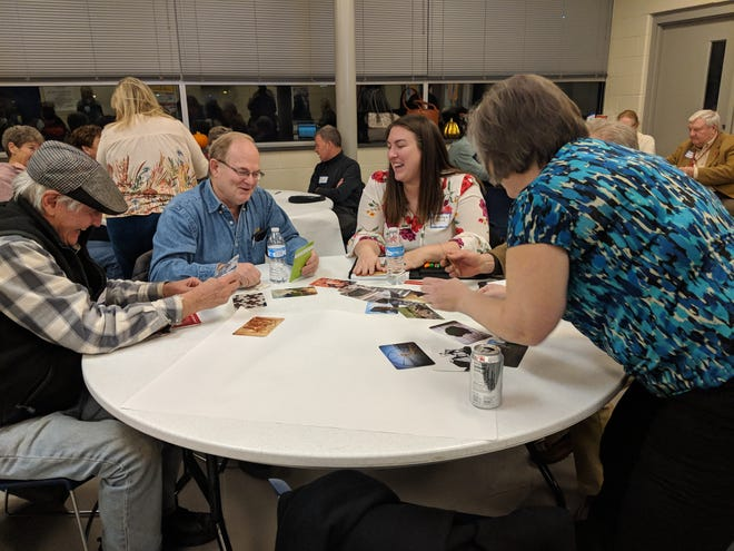 From left, East Price Hill residents Jim Shenk and Tom Gamel, Kristen Payne from Madisonville, and Sheila Rosenthal from East Price Hill on Nov. 28, 2018. Small groups discuss which photo reminds them of the Price Hill branch library.