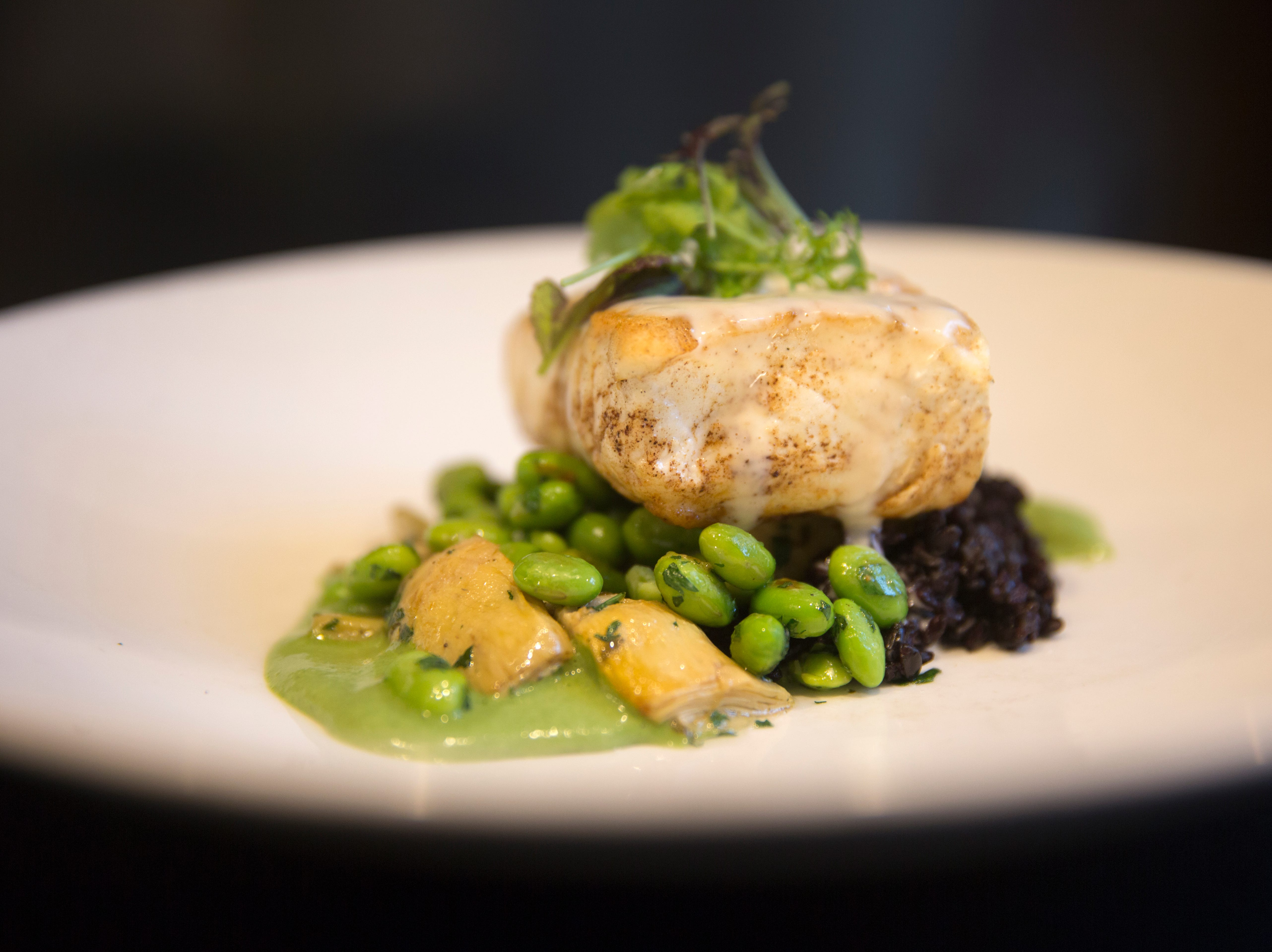 Chad Monk, The Mercer's chef de cuisine, prepares a main dish of halibut with artichoke, black rice, edamame, with sorrel cream. The dish is $36.00. The Mercer is on Vine street in Over-the-Rhine and has been serving Italian-Eureopen food since 2014. The owner, Jon Zipperstein, also owns Kaze, just up the block and Embers in Madeira. Emmy Friedrichs is the manager.